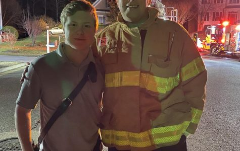 Chrisitan Davies stands with Lt Jason Elmore, the Public Information Officer for the Chesterfield County Fire Department, after a local fire had been extinguished.