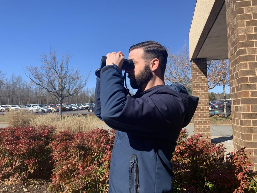 Mr. Zachary Woolard spends his lunch period watching birds outside of the Midlo Library.