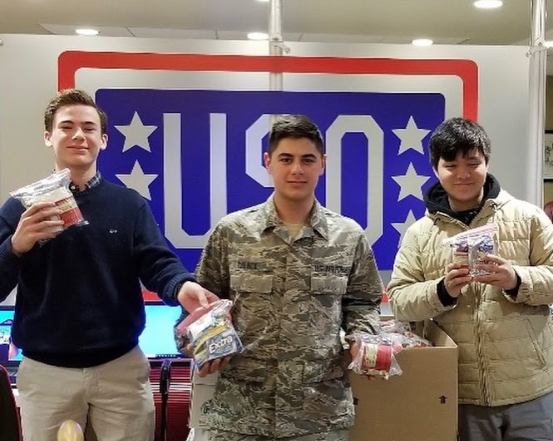 Freshmen Officers Brennan Lane and Arron Lui deliver donations to the USO.