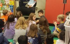 Midlo football player, junior Kameron Olds, reads to elementary students at J.B Watkins.