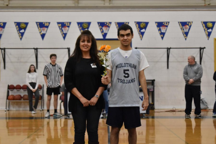 Vincent Biamonte and his mother walk onto the court for Senior Day against Meadowbrook.