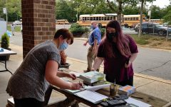 Mrs. Emilia Evans issues a textbook in Midlo Library's textbook distribution 2020.