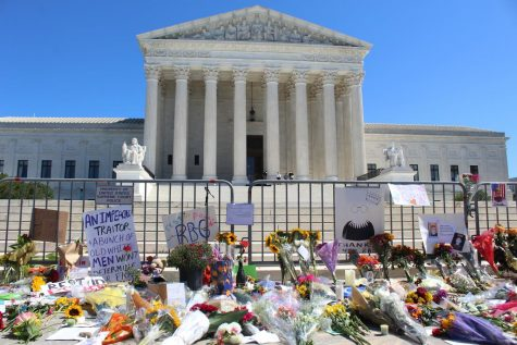 Flowers, posters, and candles fill the steps of the Unites States Supreme Court.