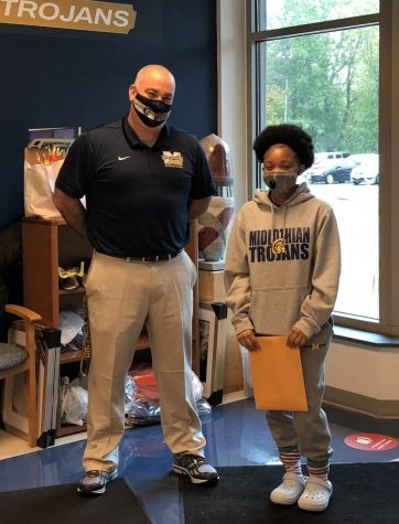 Tanaiya Turner happily accepts her Student of the Month award from Assistant Principal Mr. Steven Lagow.
