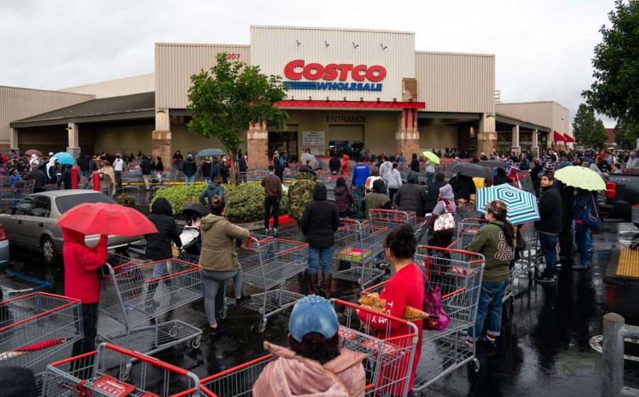 Costco members wait in long lines to enter the store. Signs outside the entrance listed out-of-stock items, with toilet paper and hand sanitizer often at the top of the list.
