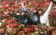 Sarah Nugent, Katie Zoe Kaze, and Camryn Kinsie sit among the collected food from their food drive.