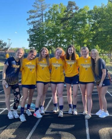 The Midlo Girls Varsity Soccer seniors gather together.