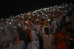 Midlo students wave their phones and sing to the beat of Sweet Caroline at their homecoming game against Cosby.
